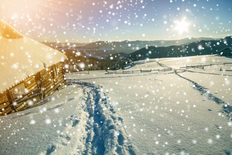 Paisaje navideño invernal Camino de huella humana en nieve blanca y profunda en una pequeña cabaña de pastor de madera, bosque de fotos de archivo