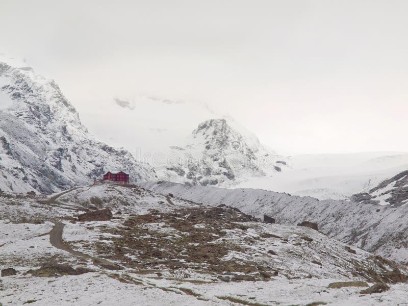 Paisaje Nevado con el camino lleno de grava Picos agudos brumosos de altas montañas en fondo imágenes de archivo libres de regalías