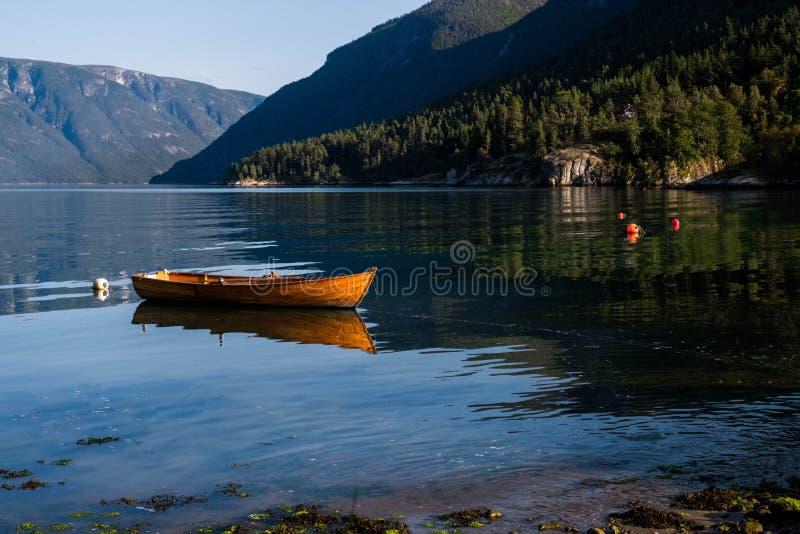 Paisaje pacífico con el barco de pesca de madera anaranjado en el río Paisaje de Noruega con las montañas en Lustrafjord fotos de archivo libres de regalías