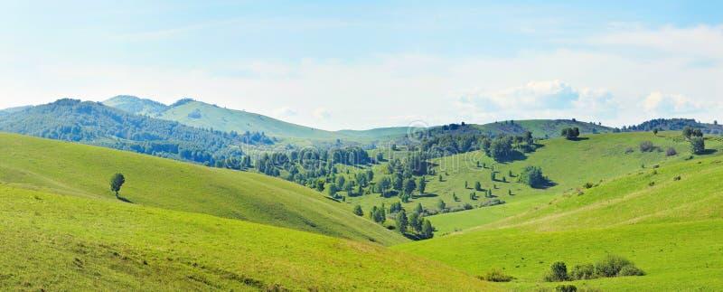 Paisaje panorámico montañoso hermoso con las colinas herbosas verdes imagen de archivo libre de regalías