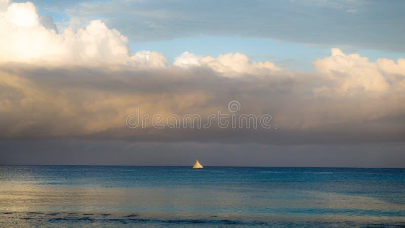 Paisaje pastoral de la puesta del sol de la superficie del mar con un velero en la República Dominicana imagenes de archivo