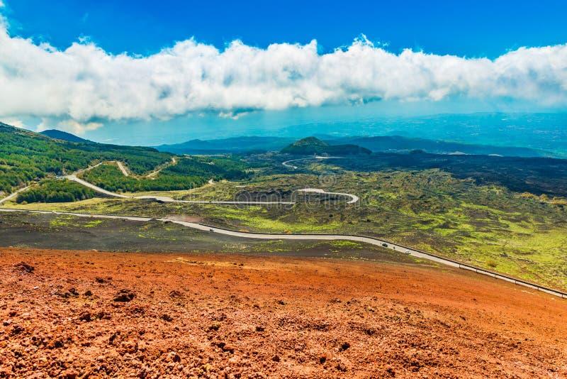 Paisaje pintoresco con el camino serpentino, las colinas coloridas de la lava cubiertas con la hierba y el bosque foto de archivo libre de regalías