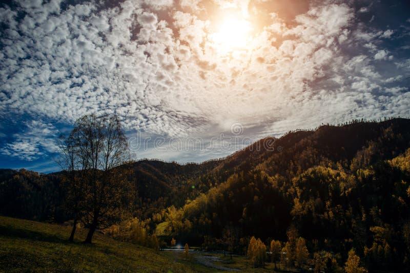 Paisaje pintoresco de las montañas que brillan intensamente bajo luz del sol Rayos fantásticos del sol con el cielo nublado azul  foto de archivo