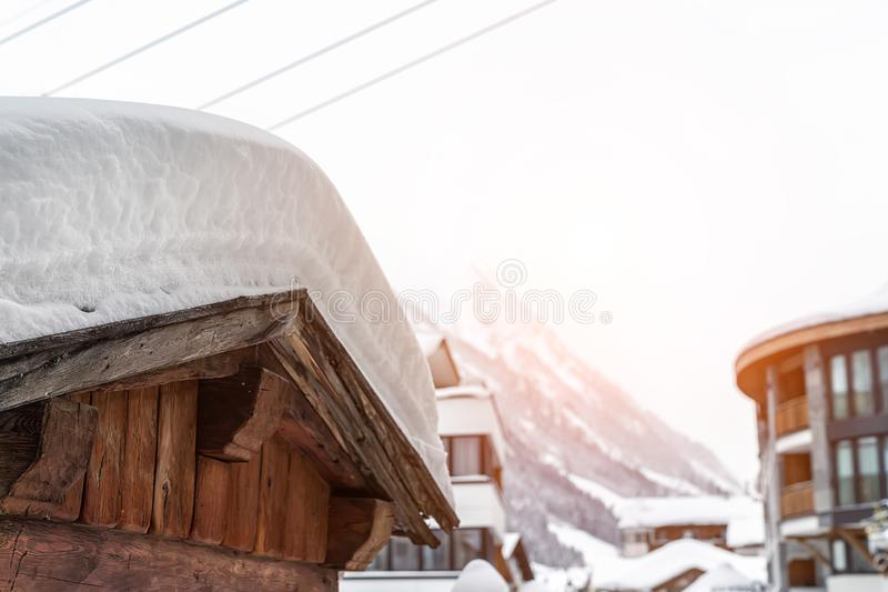 Paisaje pintoresco del pueblo alpino austríaco con techo de granero de madera cubierto de gruesa capa de nieve después de ventil imágenes de archivo libres de regalías