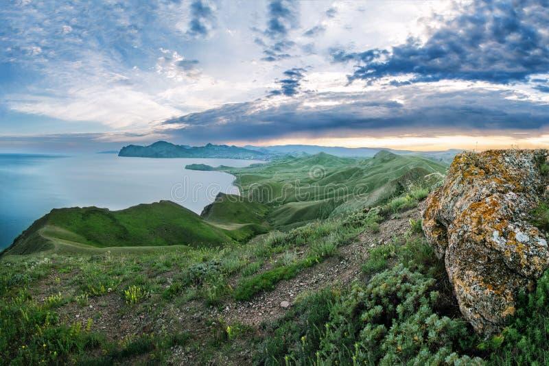 Paisaje puesta del sol en el top de montañas verdes que pasan por alto el mar imagenes de archivo