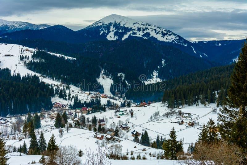 Paisaje que sorprende del pueblo de montaña ucraniano en los Cárpatos en el invierno en el amanecer fotografía de archivo