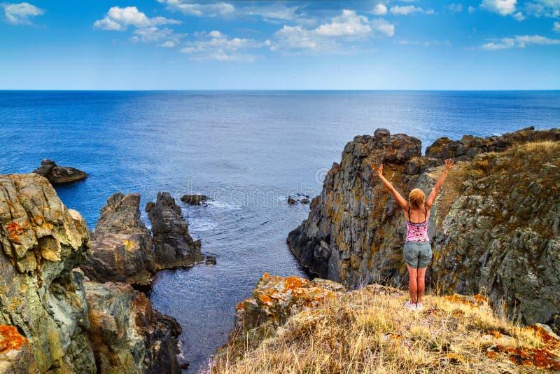 Paisaje rocoso costero - las manos de la muchacha aumentaron hasta el cielo que celebraba la libertad foto de archivo libre de regalías