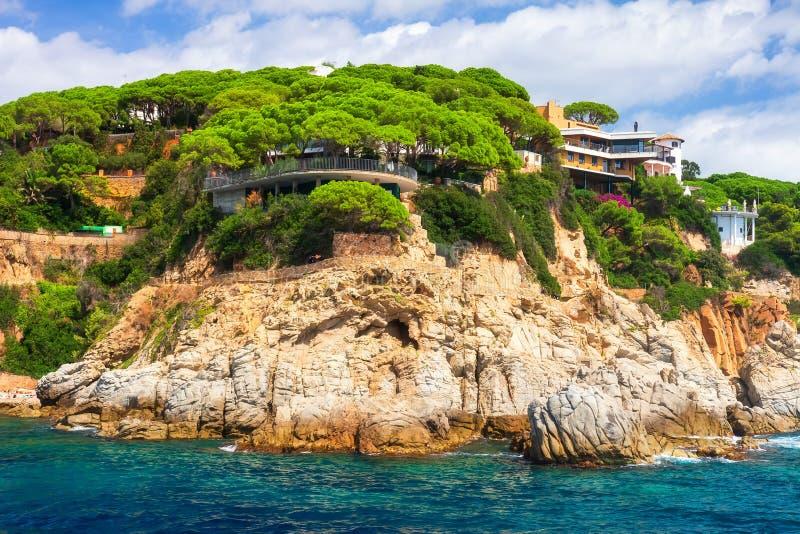 Paisaje rocoso de la costa en mediterráneo con la casa hermosa moderna en orilla de alto mar en Costa Brava, España imagen de archivo