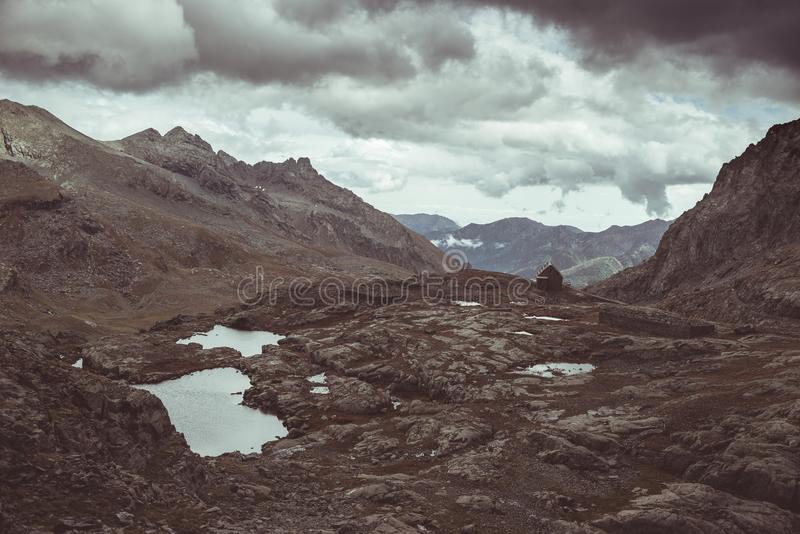 Paisaje rocoso de la mucha altitud y poco lago Paisaje alpino majestuoso con el cielo tempestuoso dramático Visión granangular de imagen de archivo