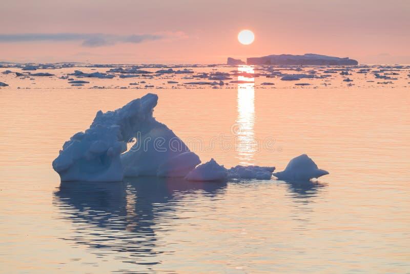 Paisaje ?rtico de la naturaleza con los icebergs en el icefjord de Groenlandia con puesta del sol/salida del sol del sol de media fotos de archivo
