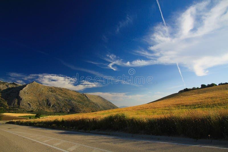 Paisaje rural bajo formaciones dramáticas de la nube del cielo en los altos llanos de Sierra Nevada imagen de archivo