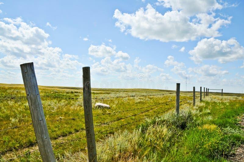Paisaje rural con la cerca a lo largo de tierras de labrantío foto de archivo libre de regalías