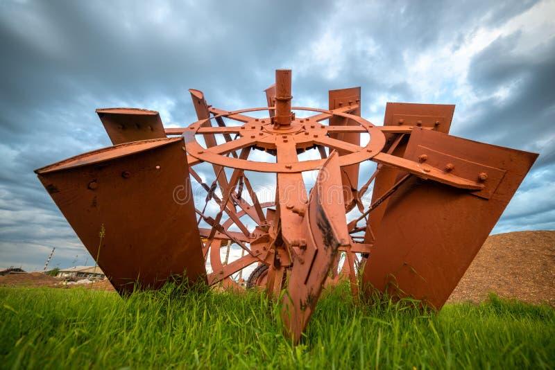 Paisaje rural con las cuchillas del vapor de paleta del vintage en hierba y el cielo azul de la tempestad de truenos imagenes de archivo
