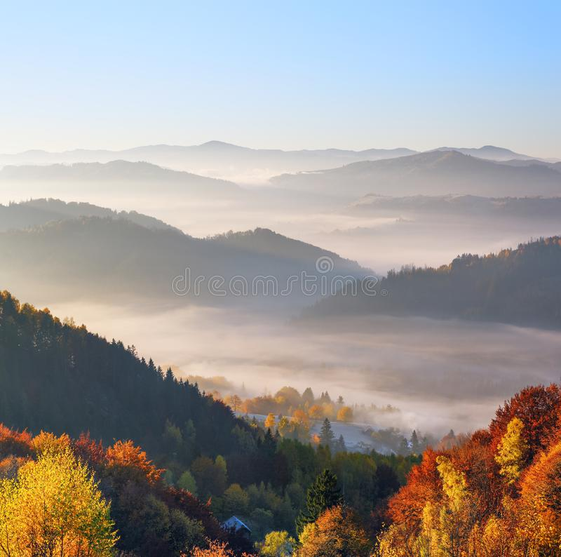 Paisaje rural del oto?o majestuoso Paisaje con las monta?as, los campos hermosos y los bosques cubiertos con niebla de la ma?ana  foto de archivo