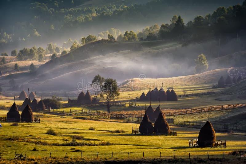 Paisaje rural hermoso de la montaña en la luz de la mañana con niebla, casas viejas y pajares imagenes de archivo