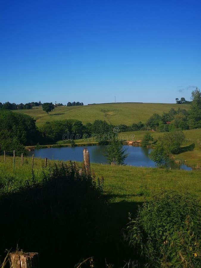 Paisaje sobre la hierba verde y un pequeño lago azul en Borgoña Francia imagen de archivo