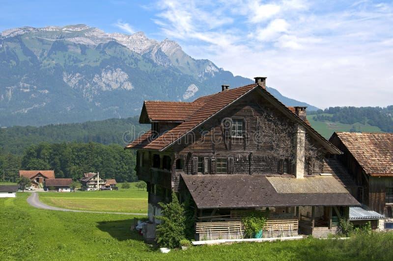 Paisaje suizo con las montañas y la granja de madera vieja imagen de archivo libre de regalías