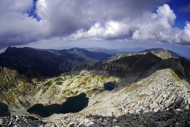 Paisaje tempestuoso en las montañas de Retezat sobre los picos y los lagos del glaciar foto de archivo