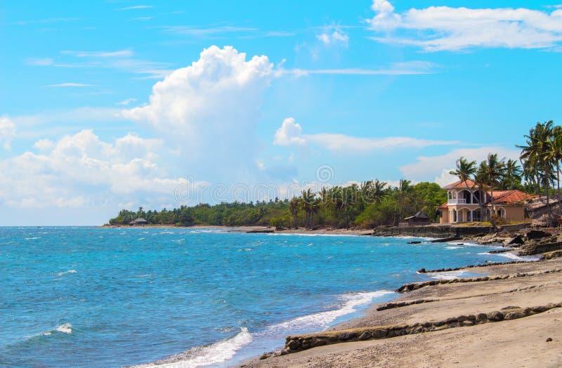 Paisaje tropical con el mar, la playa y la palmera Opinión de la playa de la arena con las palmas y la casa foto de archivo libre de regalías