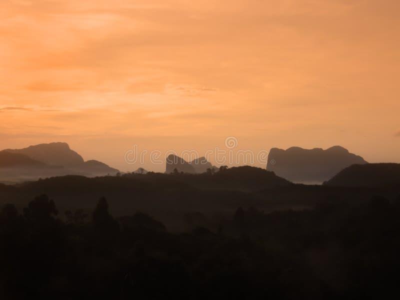 Paisaje tropical de la colina de la montaña de la capa de la silueta en la puesta del sol con el cielo amarillo anaranjado y las  foto de archivo libre de regalías