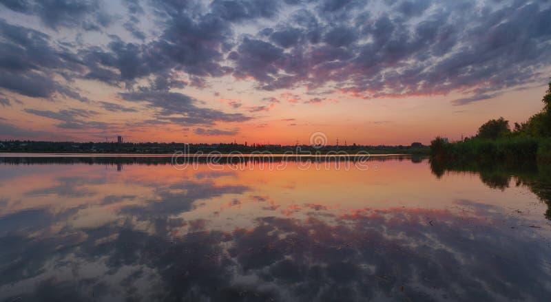 Paisaje ucraniano de la puesta del sol del verano con el cielo nublado reflejado por el agua inmóvil foto de archivo