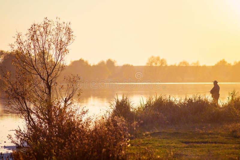 Paisaje - un río durante la puesta del sol y un pescador en el bank_ del río imagen de archivo