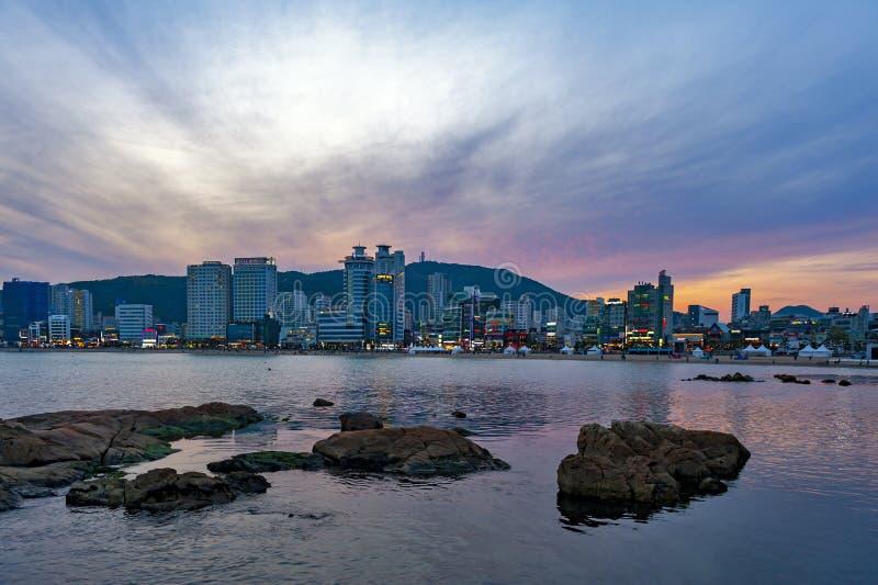 Paisaje urbano con las luces iluminadas en edificios durante puesta del sol en la playa de Gwangalli, destino turístico popular e fotografía de archivo