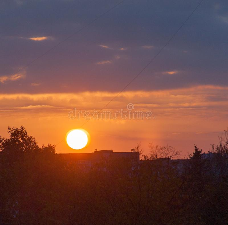 Paisaje urbano con puesta del sol y las sombras de los árboles Luz del sol a través de las nubes amarillas y azules fotografía de archivo libre de regalías