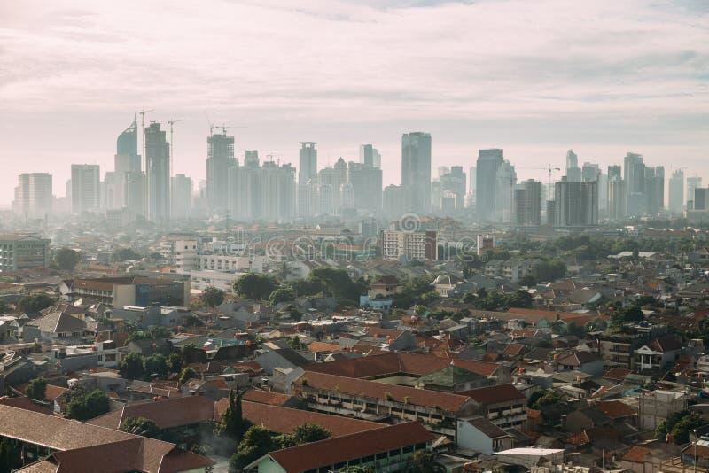 Paisaje urbano de Jakarta con alta subida, los rascacielos y los edificios locales rojos del tejado de cadera de la teja con nieb imágenes de archivo libres de regalías