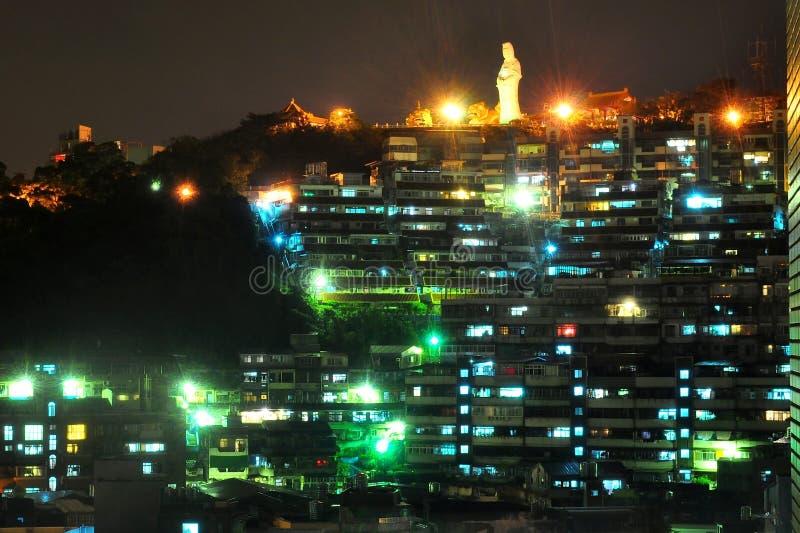 Paisaje urbano de la noche con la estatua en la cumbre