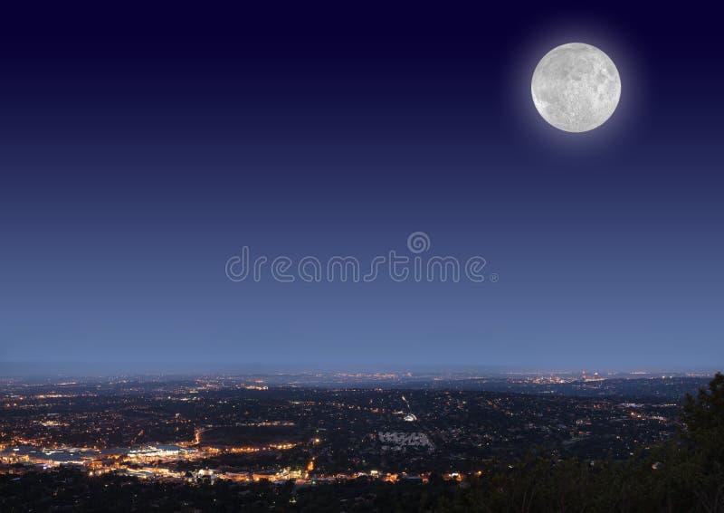 Paisaje urbano de la noche con la luna fotografía de archivo