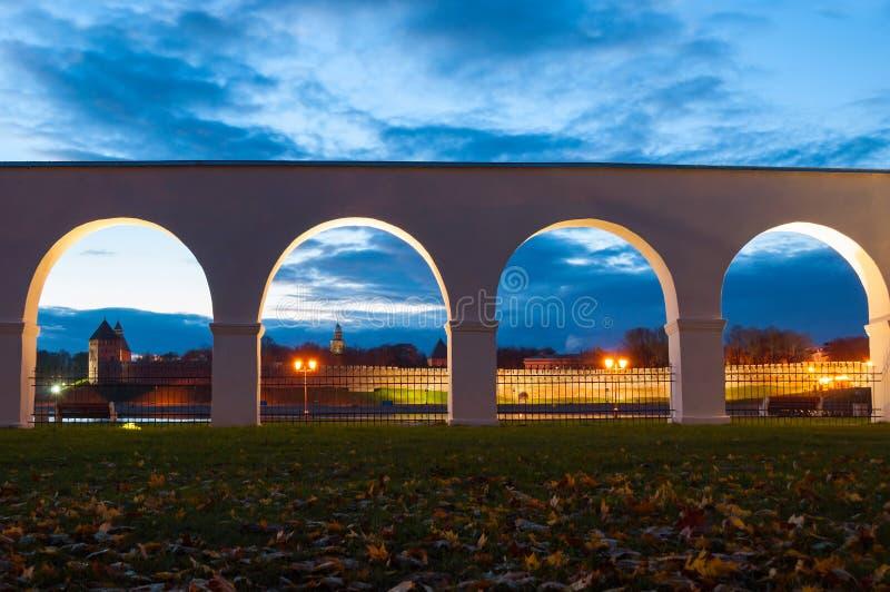 Paisaje urbano de la noche del Veliky Novgorod, Rusia Fortaleza del Kremlin en los palmos del arco de la arcada del patio de Yaro fotografía de archivo