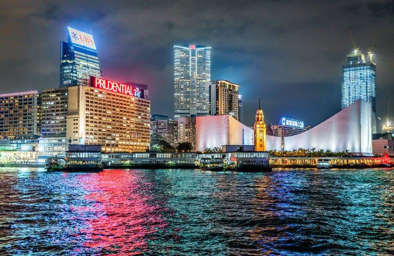 Paisaje urbano de la noche de Hong Kong Hong Kong Cultural Center, la torre de reloj y la estrella balsean los embarcaderos imagen de archivo libre de regalías