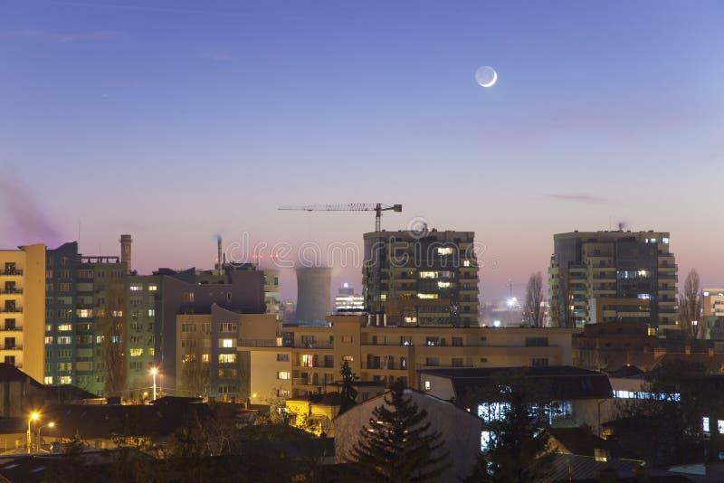 Paisaje urbano de la vecindad de Bucarest en la puesta del sol bajo encerar la luna creciente imagenes de archivo