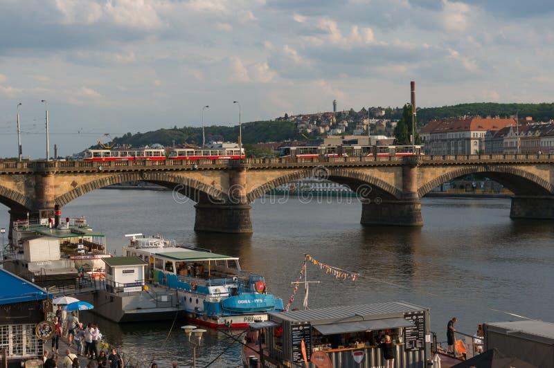 Paisaje urbano de Praga con el puente tranvía y barcos fotografía de archivo