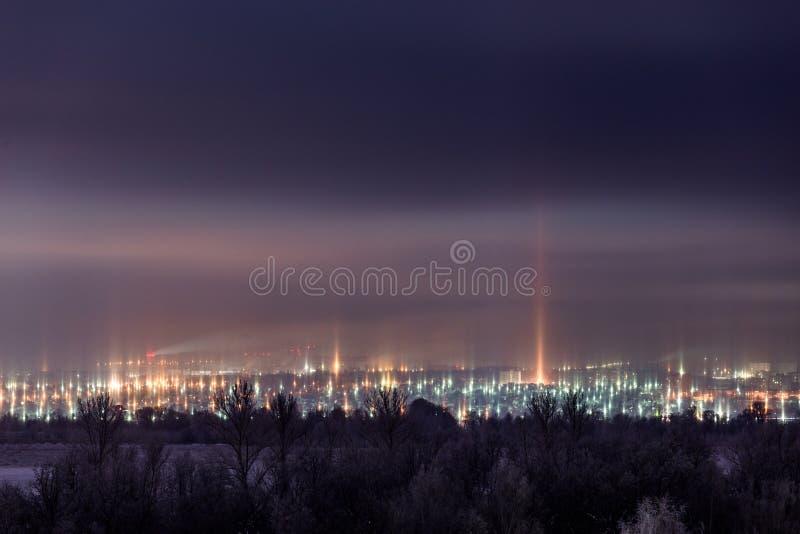 Paisaje urbano del invierno de la noche con fenómeno atmosférico de los pilares ligeros foto de archivo libre de regalías