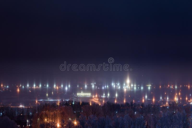 Paisaje urbano del invierno de la noche con fenómeno atmosférico de los pilares ligeros fotografía de archivo libre de regalías