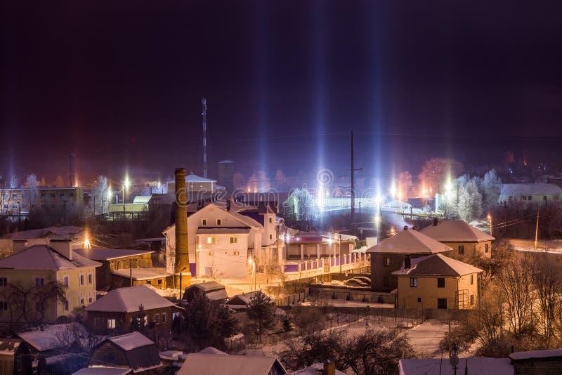 Paisaje urbano del invierno de la noche con fenómeno atmosférico de los pilares ligeros fotos de archivo