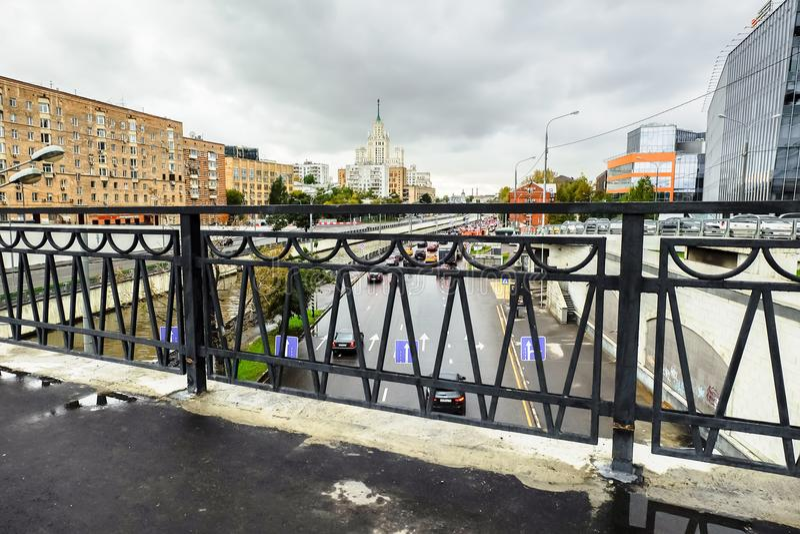 Paisaje urbano en día lluvioso Vista del terraplén del río de Yauza a través del puente Visokoyauzskiy, Moscú, Rusia imagen de archivo
