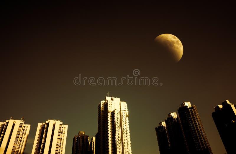 Paisaje urbano en el cielo de la noche y de la oscuridad con la media luna fotografía de archivo