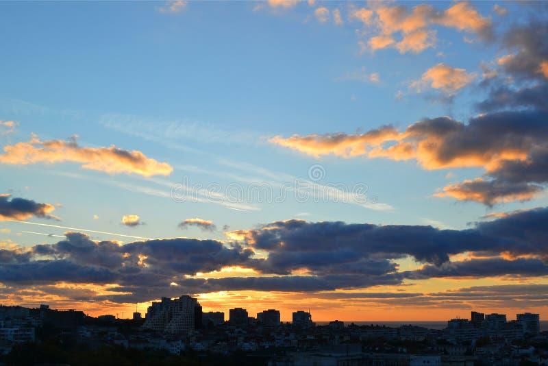 Paisaje urbano en la madrugada: el cielo azul y las nubes son coloreados amarillo-naranja por el sol naciente sobre la ciudad el  imagenes de archivo