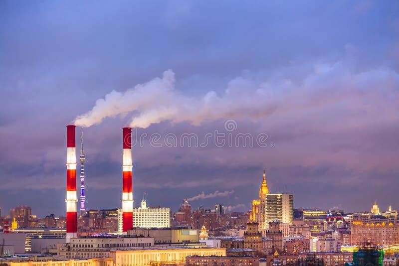 Paisaje urbano urbano industrial Los tubos de la fábrica de una ciudad ajardinan en Moscú, Rusia durante puesta del sol foto de archivo