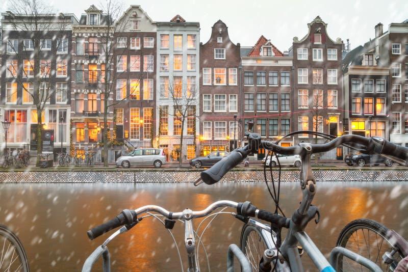 Paisaje urbano - opinión del invierno de bicicletas a las casas con las decoraciones festivas y de un canal con los barcos, ciuda foto de archivo libre de regalías
