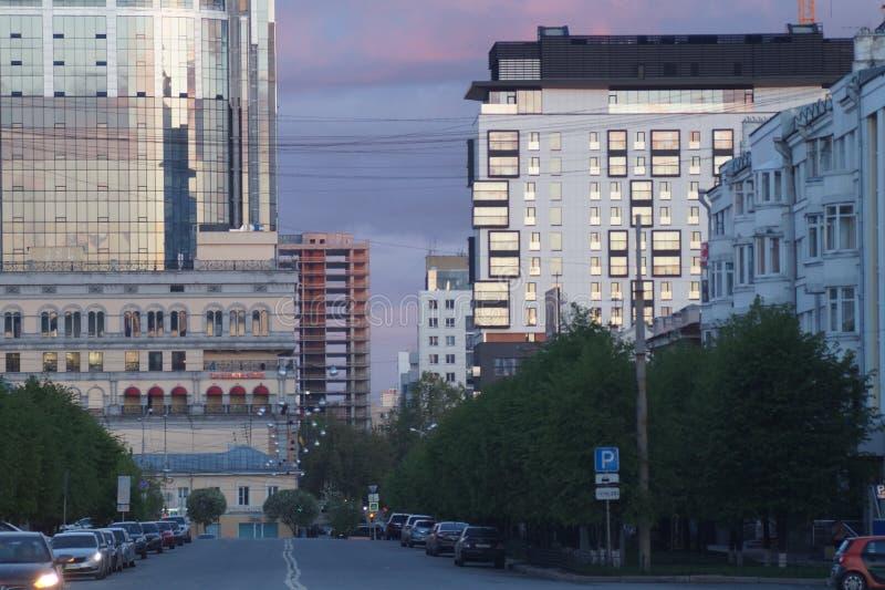 Paisaje urbano: visión desde la calle de Pushkin La puesta del sol colorea el cielo y el vidrio de edificios fotografía de archivo