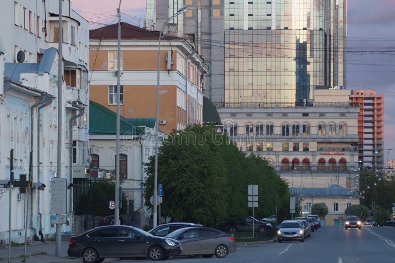 Paisaje urbano: visión desde la calle de Pushkin La puesta del sol colorea el cielo y el vidrio de edificios foto de archivo