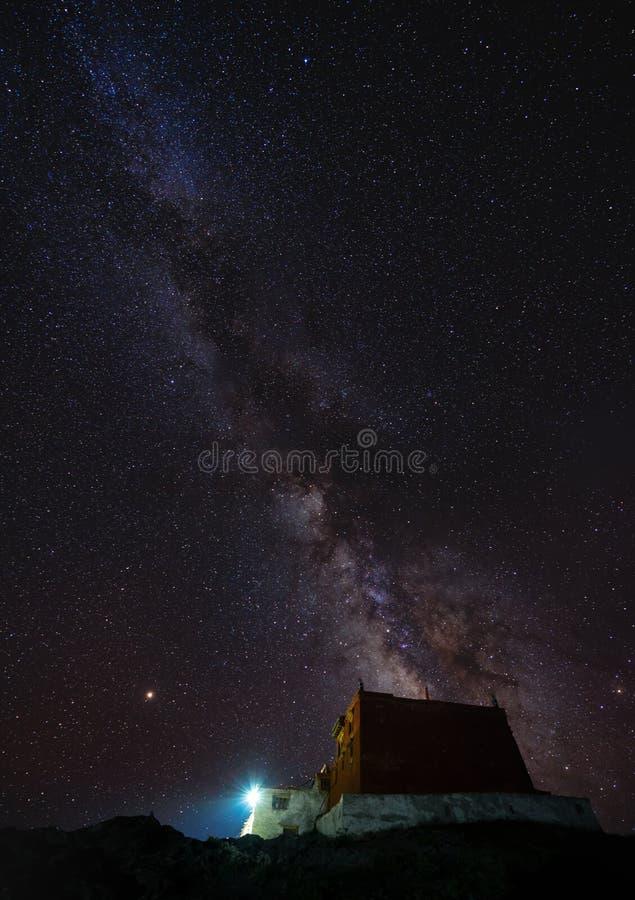 Paisaje vertical, cielo nocturno por completo de la estrella y vía láctea con el templo antiguo en el monasterio de Rangdum en la imagenes de archivo
