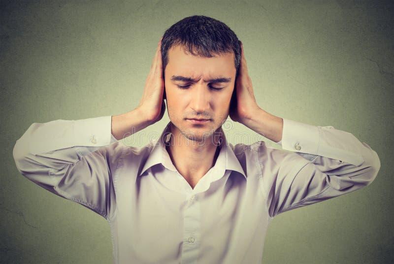 Paisible, tranquille, semblant décontracté, le jeune homme avec des yeux a fermé couvrir ses oreilles photos libres de droits