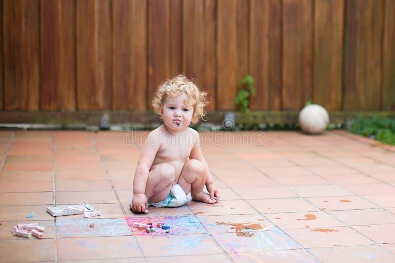 paiting与白垩的滑稽的矮小的女婴 免版税库存图片