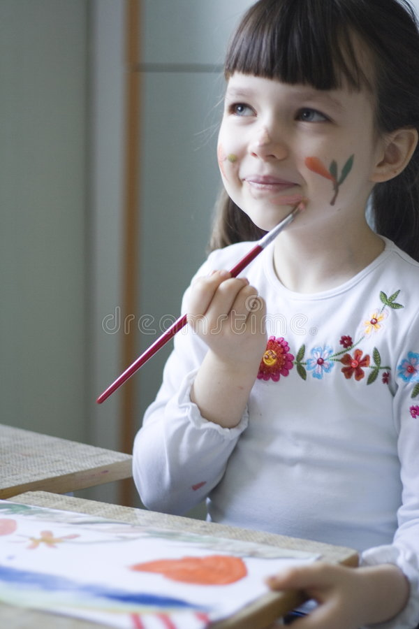 Paiting girl. Girl painting her face royalty free stock photography