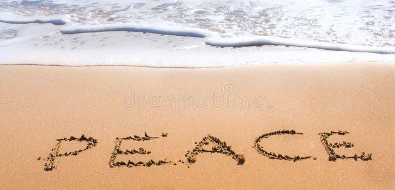 Paix écrite en sable sur la plage photographie stock libre de droits